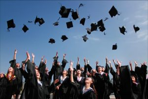 There are many graduated students in their black and white uniforms throwing their hats up in the air.