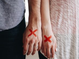Two hands next to each other with a red ex marked on them.