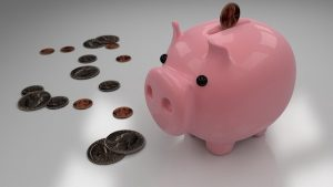 A pink piggy bank and coins.
