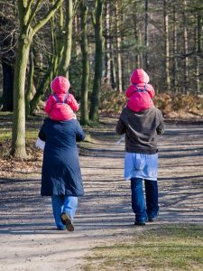 Parents with twins walking.