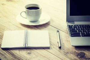 A notebook, coffee, laptop, and a pen on the desk.