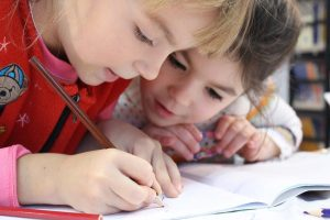 Kids occupied by drawing in a notebook while you prepare for moving with kids during school year.
