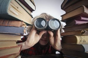 A person surrounded by books looking through binoculars