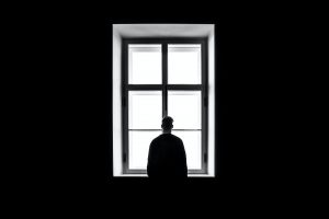 A person in a dark room looking through the window. One of the disadvantages of living off-campus is that it can lead to the feeling of social isolation.