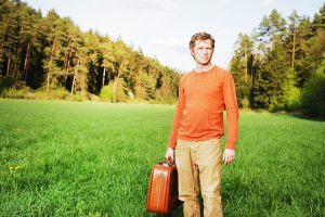 Man with a bag is planning on leaving. If you are thinking about the same thing, well, learn how can moving away help you get over a heartbreak.