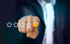 A finger pointing on star reviews. When hiring movers for a local move, you have to check the reviews.